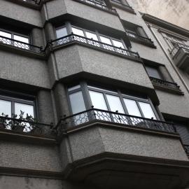 Ventanas y balcones en edificio de seis plantas en Ourense